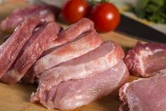 Skivor av rått fläskkotlettkött på träskärbräda Arkivfoton