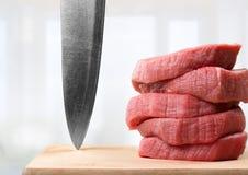 Skivor av rått kött med den skarpa kniven Fotografering för Bildbyråer