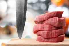 Skivor av rått kött med den skarpa kniven Royaltyfria Bilder