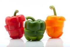 Skivor av röd, grön och orange peppar som isoleras på vitbakgrund Royaltyfri Foto