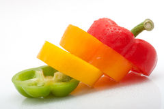 Skivor av rött, görar grön, gulingen och orange peppar som isoleras på vitbakgrund Royaltyfri Bild
