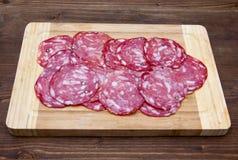 Skivor av salami på skärbräda på trä Royaltyfri Fotografi