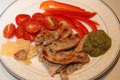 Skivor av stekkalkon med tomaten, röd peppar, skivor av ost och pesto Fotografering för Bildbyråer