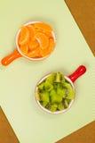 Skivor av tangerin och kiwin i en kopp Royaltyfri Bild