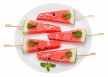 Skivor av vattenmelon med pinnen på den vita plattan på vit Arkivfoto