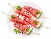 Skivor av vattenmelon med pinnen på den vita plattan på vit Arkivfoton