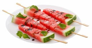 Skivor av vattenmelon med pinnen på den vita plattan på vit Arkivbilder