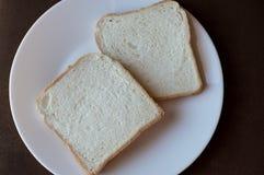 2 skivor av vitt bröd på en vit platta royaltyfri bild