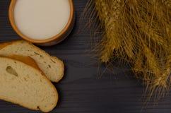 Skivor av vitt bröd, veteöron och mjölkar på en svart tabell Royaltyfri Foto