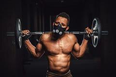 Skivstång för stark man för afrikansk amerikan idrotts- hållande på skuldror i idrottshall svarta mannen poserar med skivstången  Arkivbilder