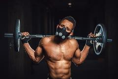 Skivstång för stark man för afrikansk amerikan idrotts- hållande på skuldror i idrottshall svarta mannen poserar med skivstången  Royaltyfri Fotografi