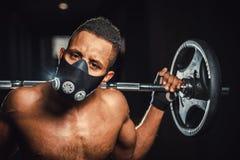 Skivstång för stark man för afrikansk amerikan idrotts- hållande på skuldror i idrottshall svarta mannen poserar med skivstången  Royaltyfri Bild