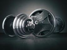 Skivstång och dumbell Sportbodybuildingutrustning på svart tillbaka Arkivfoto