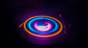 Skivtallriken som spelar vinyl med glödande abstrakt begrepp, fodrar begrepp på mörk bakgrund Fotografering för Bildbyråer