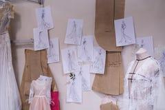 Skizzen von den Kleidern, die in einem Hochzeitsstudio hängen Lizenzfreie Stockfotos