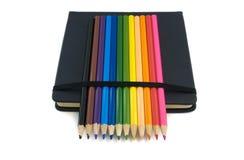 Skizzenbuch und farbige Bleistifte lokalisiert Stockfotografie
