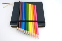Skizzenbuch und farbige Bleistifte lokalisiert Lizenzfreie Stockfotos