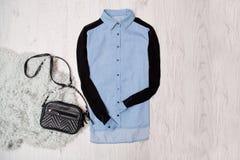 Skjorta för jeanskvinna` s, svart handväska på den konstgjorda pälsen Trendigt begrepp, träbakgrund, bästa sikt Arkivbild