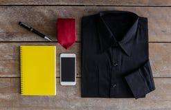 Skjorta slipsar, smartphone, anteckningsbok, penna på träbakgrund Arkivfoton