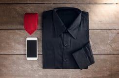 Skjorta slipsar, smartphone på träbakgrund Arkivbilder