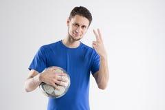 Skjortan för blått för fotbollspelaren med bollen isolerade studion Royaltyfri Bild