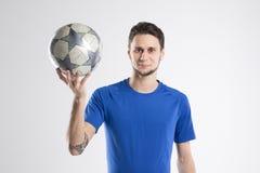 Skjortan för blått för fotbollspelaren med bollen isolerade studion Royaltyfria Bilder
