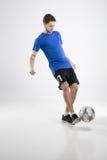 Skjortan för blått för fotbollspelaren med bollen isolerade studion Royaltyfria Foton