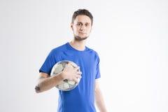 Skjortan för blått för fotbollspelaren med bollen isolerade studion Royaltyfri Fotografi