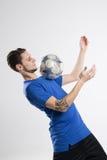 Skjortan för blått för fotbollspelaren med bollen isolerade studion Arkivfoton