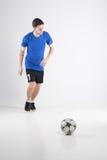 Skjortan för blått för fotbollspelaren med bollen isolerade studion Royaltyfri Foto