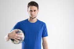 Skjortan för blått för fotbollspelaren med bollen isolerade studion Arkivfoto