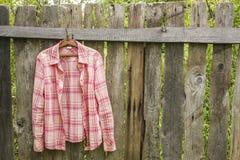 Skjortan hänger a på hängare på det gamla staketet från bräden i en villag royaltyfri bild