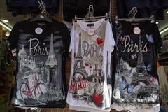 Skjortor med den Paris logoen på försäljning i den Montmartre souvenir shoppar i Paris, Frankrike arkivbilder