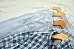 4 skjortor på trästolar som förläggas på sängen i skuggor av vit, fotografering för bildbyråer
