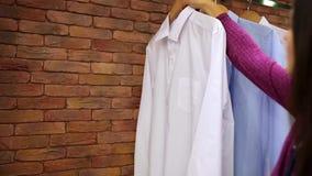 Skjortor som hänger på en hängare i lagret arkivfilmer