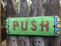 Skjut det färgrika målade gröna trätecknet för tecknet på ett bekymrat staket royaltyfri foto