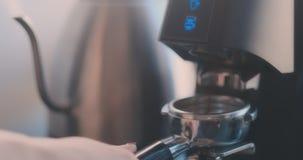 Skjut precis knappen Nytt jordkaffe i portafilter B?nor f?r Barista pluggh?stkaffe genom att anv?nda kaffemaskinen Kaffe arkivfilmer
