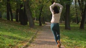 Skjuta bakifrån, dansar den Caucasian kvinnlign för den härliga brunetten i latinsk stil på bana i Green Park i vår arkivfilmer