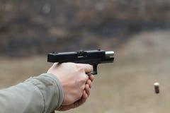 Skjuta från en pistol Tillbakaläggande av vapnet Mannen siktar på målet Skjutbana Man skottlossningusppistolen på målet in ut Royaltyfri Foto