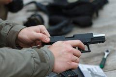 Skjuta från en pistol Tillbakaläggande av vapnet Mannen siktar på målet Skjutbana Man skottlossningusppistolen på målet i ind Fotografering för Bildbyråer