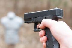 Skjuta från en pistol Tillbakaläggande av vapnet Mannen siktar på målet Skjutbana Man skottlossningusppistolen på målet i ind Arkivfoton