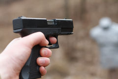 Skjuta från en pistol Tillbakaläggande av vapnet Mannen siktar på målet Skjutbana Man skottlossningusppistolen på målet i ind Royaltyfria Foton