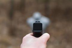 Skjuta från en pistol Tillbakaläggande av vapnet Mannen siktar på målet Skjutbana Man skottlossningusppistolen på målet i ind Royaltyfri Fotografi