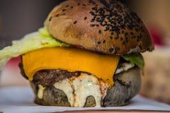 Skjuta in hamburgaren med saftig hamburgareost och blandningen av grönsaker Royaltyfri Bild