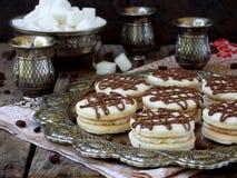 Skjuta in kakor med kräm som dekoreras med choklad på ett metalluppläggningsfat Royaltyfri Bild