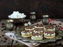 Skjuta in kakor med kräm som dekoreras med choklad på ett metalluppläggningsfat och, strila med kaffebönor omkring Arkivbilder