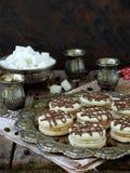 Skjuta in kakor med kräm som dekoreras med choklad på ett metalluppläggningsfat och, strila med kaffebönor omkring Royaltyfria Bilder