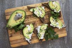 Skjuta in med avokadot, mörkt bröd och ost för vitt ljus på trä Arkivfoto