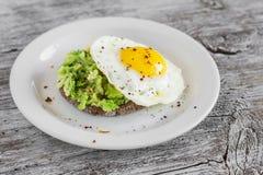 Skjuta in med avokadot och ett stekt ägg på en vit platta royaltyfri bild