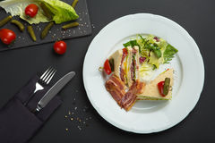 Skjuta in med bacon och grönsaker på svart bakgrund frukost- eller lunchmaträtt arkivbilder